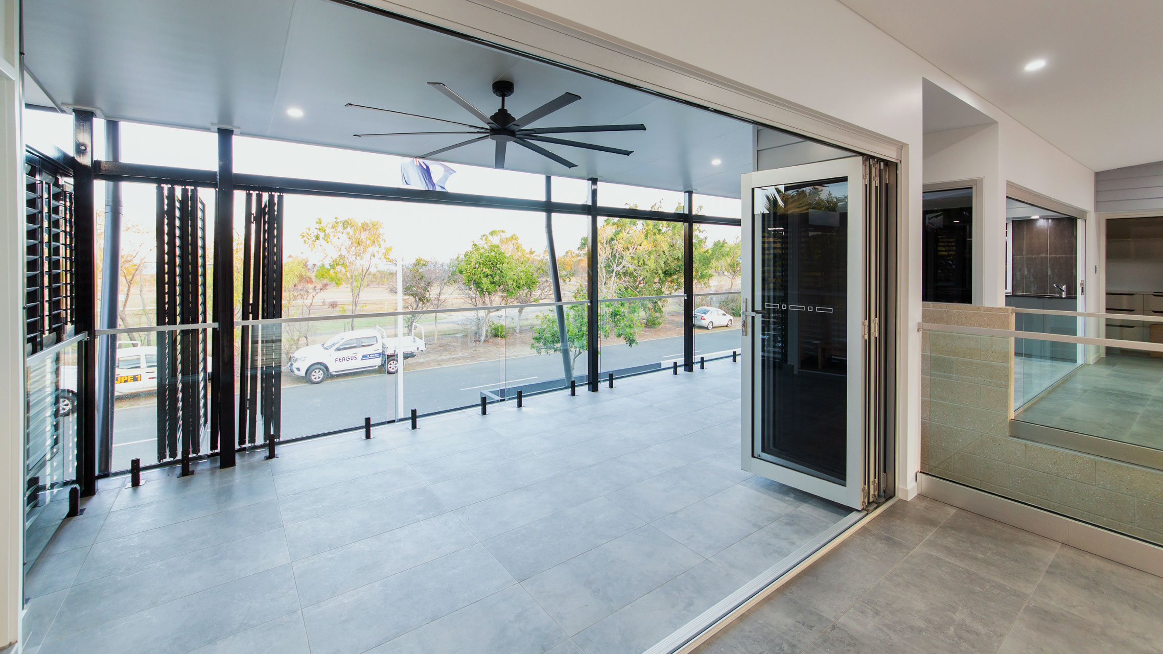 Aluminium Bifold Doors with grey glass opening to a balcony