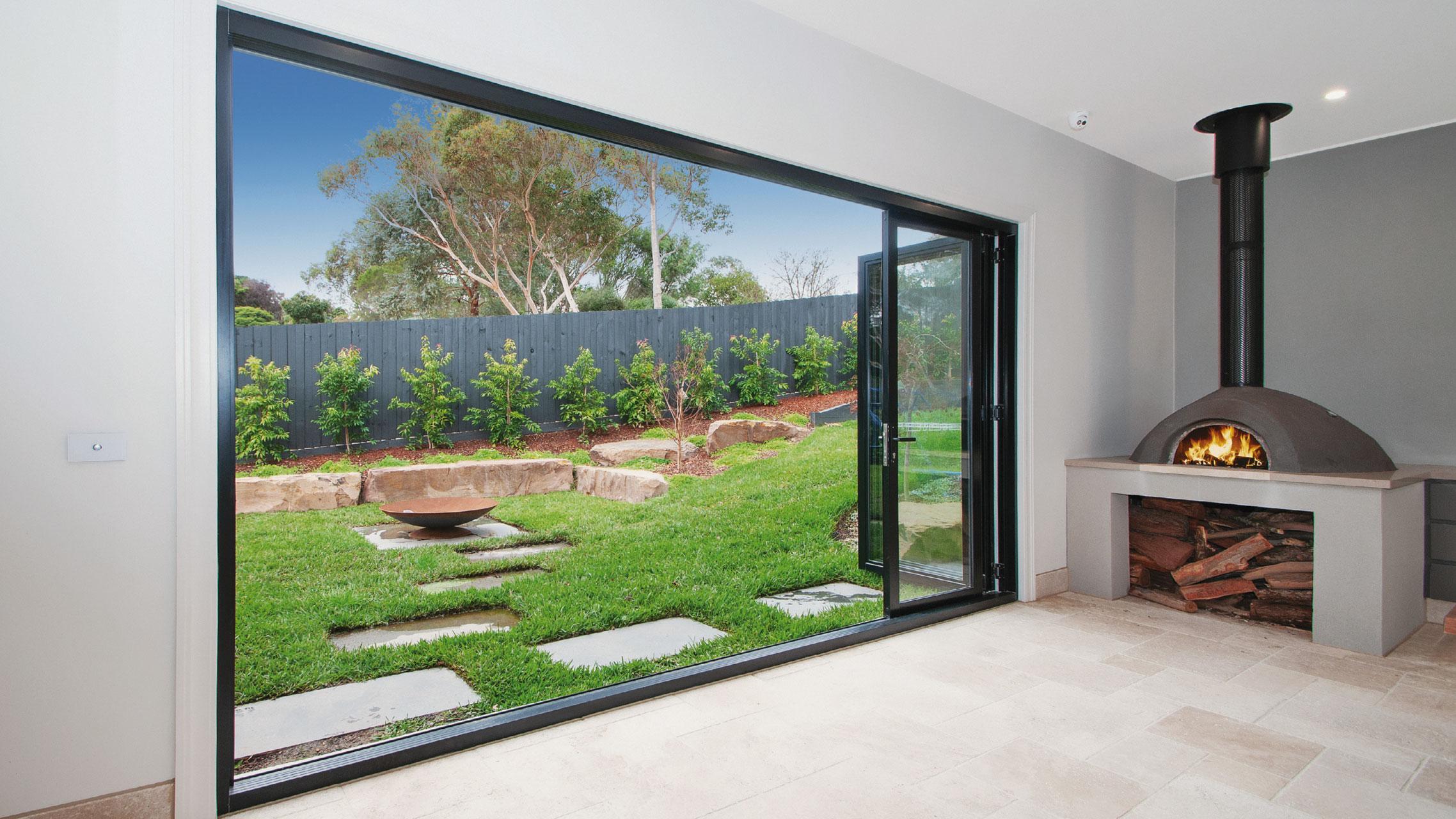 Black Aluminium Bi fold Doors opening to a landscape yard