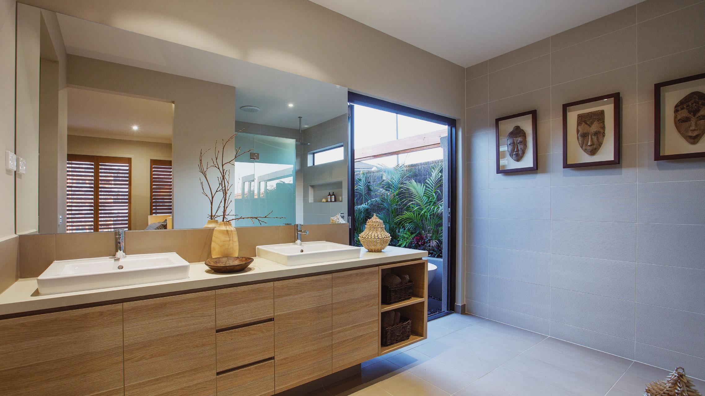 Large Frameless Bathroom Mirror above a vanity next to a bi fold door